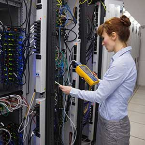 female technician taking a reading from a server rack