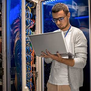 man with laptop in server room